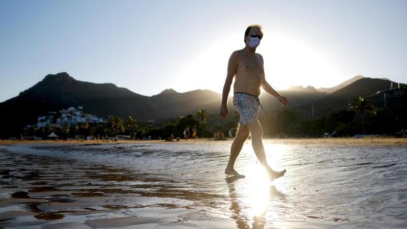 An den Mundschutz hat man sich gewöhnt - das gilt auch auf Reisen. Foto: Andres Gutierrez/dpa/dpa-tmn