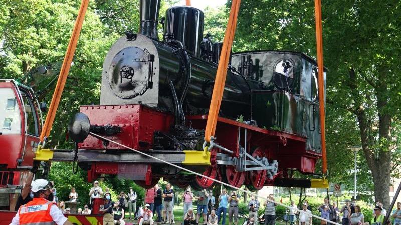 Ein Kran hievt die Dampflokomotive der früheren Kleinbahn durch das Teufelsmoor auf ihren Denkmal-Sockel. Foto: Friedemann Kohler/dpa