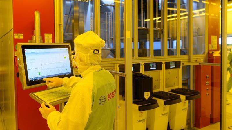 Ein Mitarbeiter steht in der neuen Halbleiterfabrik von Bosch an einer Maschine. Foto: Robert Michael/dpa-Zentralbild/dpa/Symbolbild