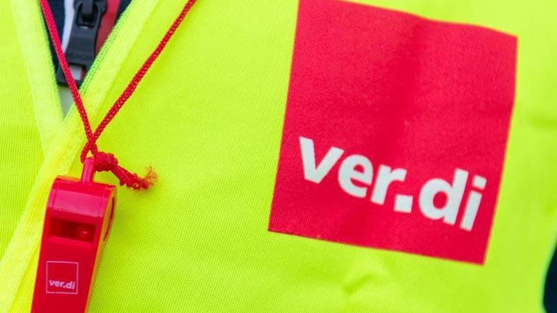 Ein Streikender trägt eine Warnweste mit dem Verdi-Logo. Foto: Christophe Gateau/dpa/Symbolbild