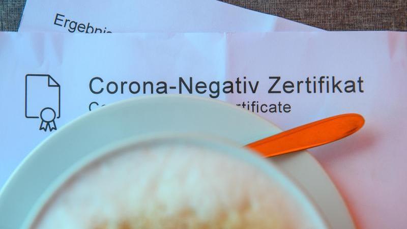Ein Milchkaffee steht in einem Café auf einem Tisch auf einem Corona-Negativ Zertifikat. Foto: Klaus-Dietmar Gabbert/dpa-Zentralbild/dpa/Symbolbild