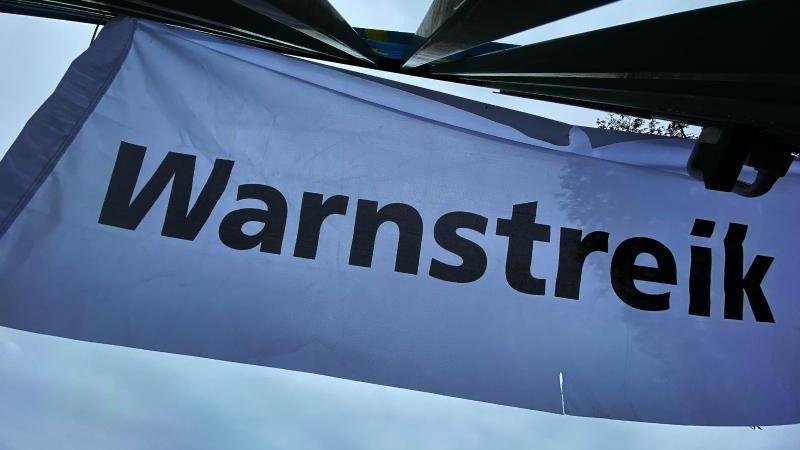 """""""Warnstreik"""" steht auf einem Transparent. Foto: Paul Zinken/dpa/Symbolbild"""