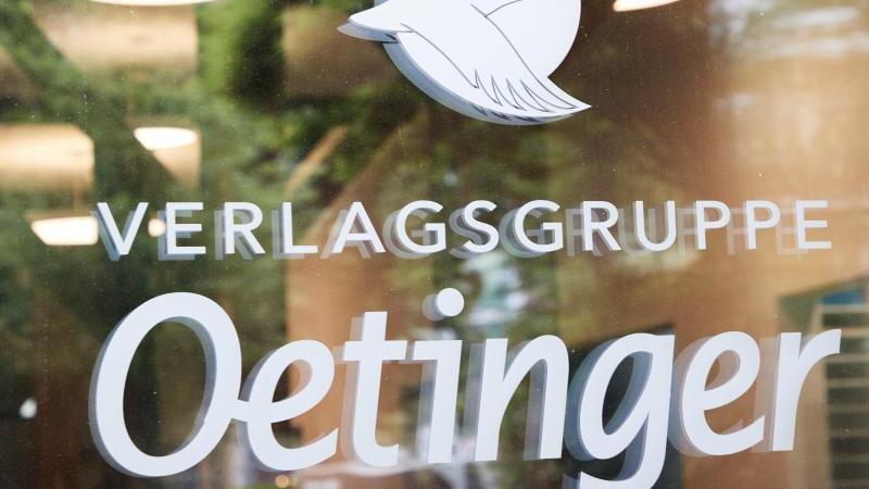 """Ein Logo und der Schriftzug """"Verlagsgruppe Oetinger"""" steht an einer Glasscheibe. Foto: Georg Wendt/dpa/Archivbild"""