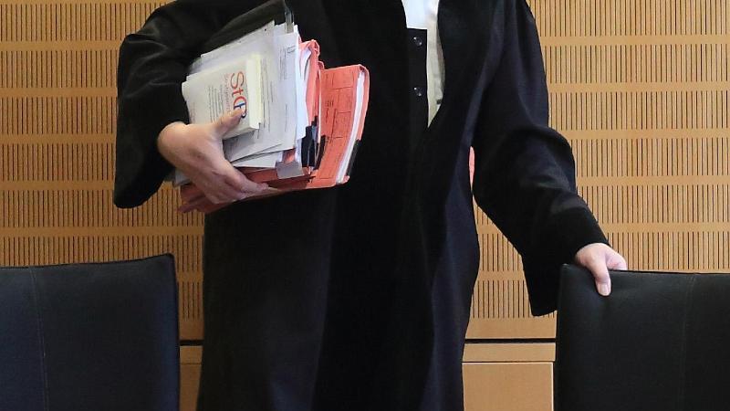 Ein Richter rückt in einem Verhandlungssaal seinen Stuhl zurecht. Foto: Jens Wolf/dpa/Archivbild