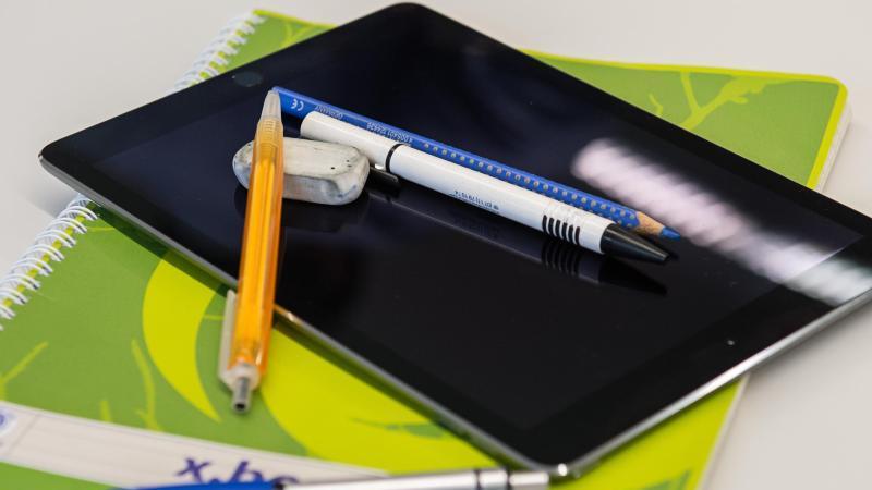 Ein Tablet auf Unterrichtsmaterialien. Foto: Wolfram Kastl/dpa/Archiv