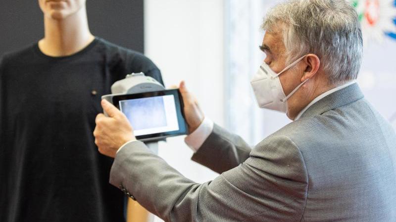 Herbert Reul (CDU) hält die neue Infrarotkamera KTvisio vor ein Shirt, auf dem Schmauchspuren sichtbar werden. Foto: Marcel Kusch/dpa