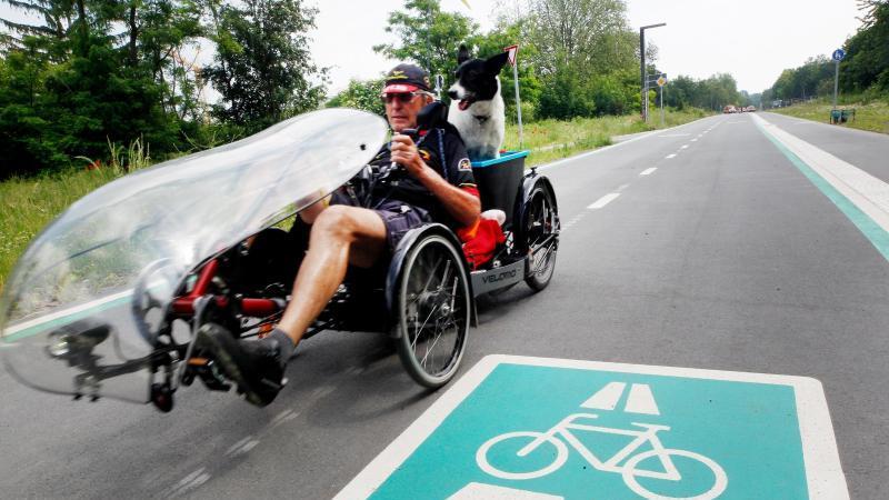 Auf dem Liegerad fährt Peter Hoffmann mit seinem Hund Charly über die neue Straße. Foto: Roland Weihrauch/dpa