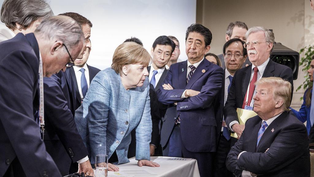 HANDOUT - 09.06.2018, Charlevoix, La Malbaie, Quebec, Kanada: Bundeskanzlerin Angela Merkel (CDU, M) spricht mit US-Präsident Donald Trump (r) während der Beratungen am Rande der offiziellen Tagesordnung. Emmanuel Macron (2.v.l), Präsident von Frankr