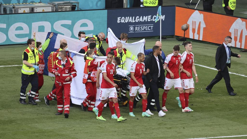 Ratownicy medyczni używają noszy, aby wyciągnąć duńskiego Christiana Eriksena z boiska po tym, jak upadł podczas meczu o mistrzostwo Europy w piłce nożnej grupy B między Danią a Finlandią na Parken Arena w Kopenhadze w Danii, sobota, 12 czerwca 2021 r.