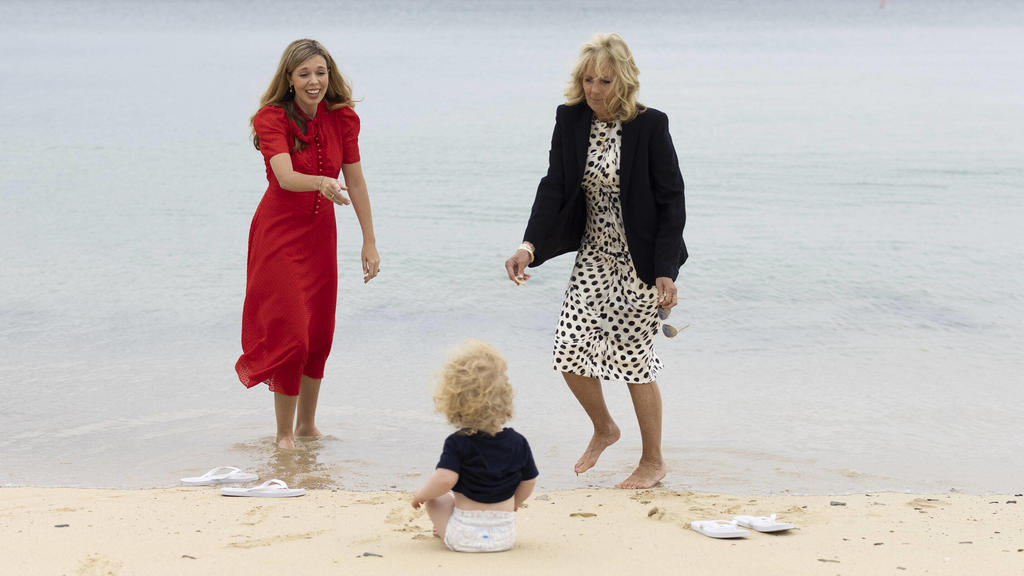 Carrie Johnson, the wife of Prime Minister Boris Johnson, speaks with First Lady of the United States Dr. Jill Biden as Wilfred Johnson sits on the beach during the G7 Leaders Summit in Carbis Bay, Cornwall, United Kingdom, on June 10, 2021. PUBLICA