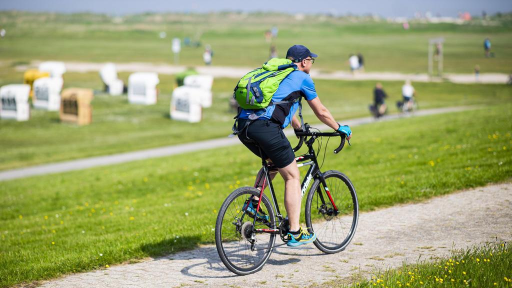 Urlaub in Deutschland Fahrradfahrer machen an der Strandpromenade im Urlaubsort Schillig eine Fahrradtour. Foto: Kirchner-Media/Wedel Schillig Niedersachsen Deutschland *** Vacation in Germany cyclists make a bicycle tour at the beach promenade in th