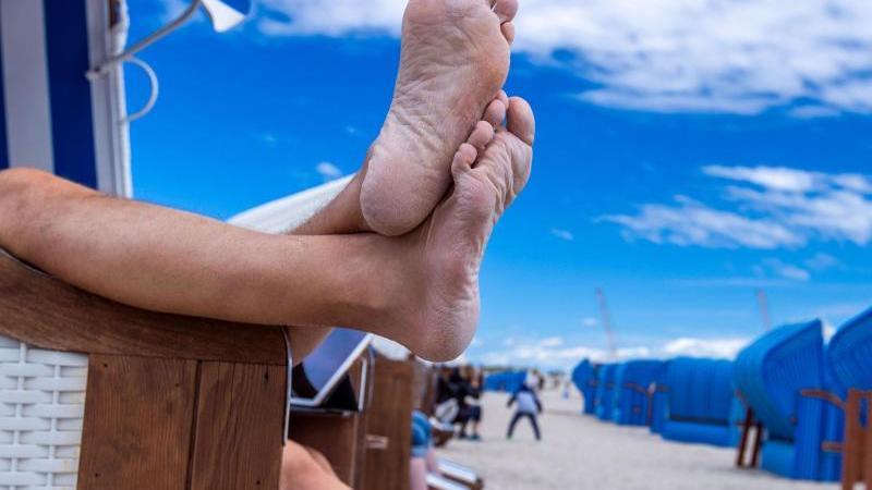 Füße hochlegen und den Urlaub genießen: Das wünschen sich viele. Foto: Jens Büttner/dpa-Zentralbild/dpa-tmn