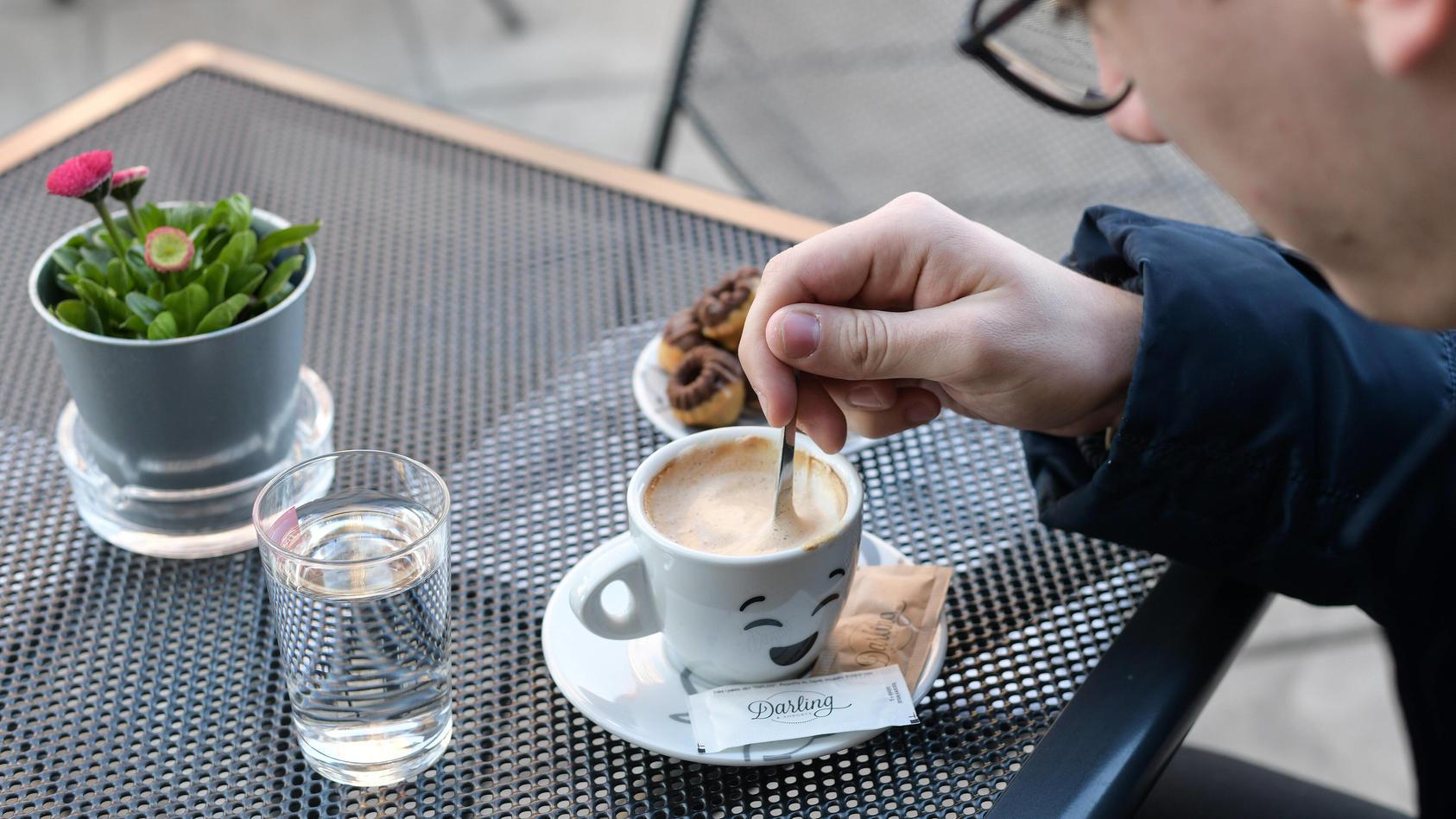 Mann in Café rührt in seinem Kaffee.