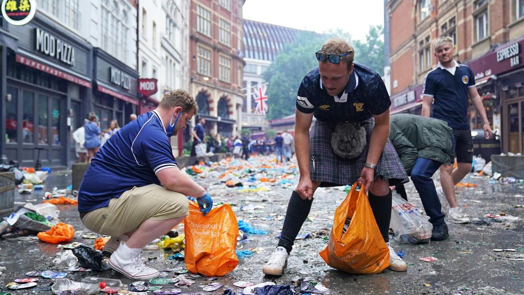 18.06.2021, Großbritannien, London: Fußball: EM, England - Schottland, Vorrunde, Gruppe D, 2. Spieltag, vor dem Spiel: Schottische Fans sammeln Müll und räumen in der Irving Street auf. Foto: Kirsty O'connor/PA Wire/dpa +++ dpa-Bildfunk +++