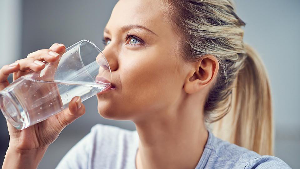 Eine junge Frau trinkt stilles Wasser aus einem Glas.