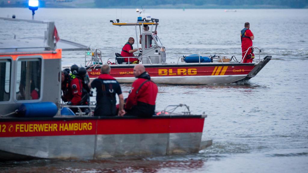 18.06.2021, Hamburg: Kleinboote von DLRG und Feuerwehr fahren bei der Suche über die Elbe. Feuerwehr und Polizei haben am Abend zweieinhalb Stunden nach einem jungen Mann gesucht, der von einem Signalturm in die Elbe gesprungen und nicht mehr aufgeta