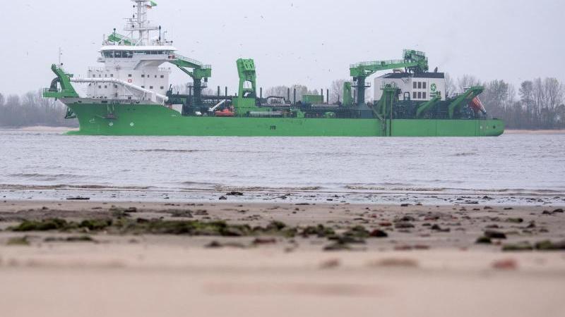 Ein Baggerschiff fährt auf der Elbe. Foto: Daniel Bockwoldt/Archivbild