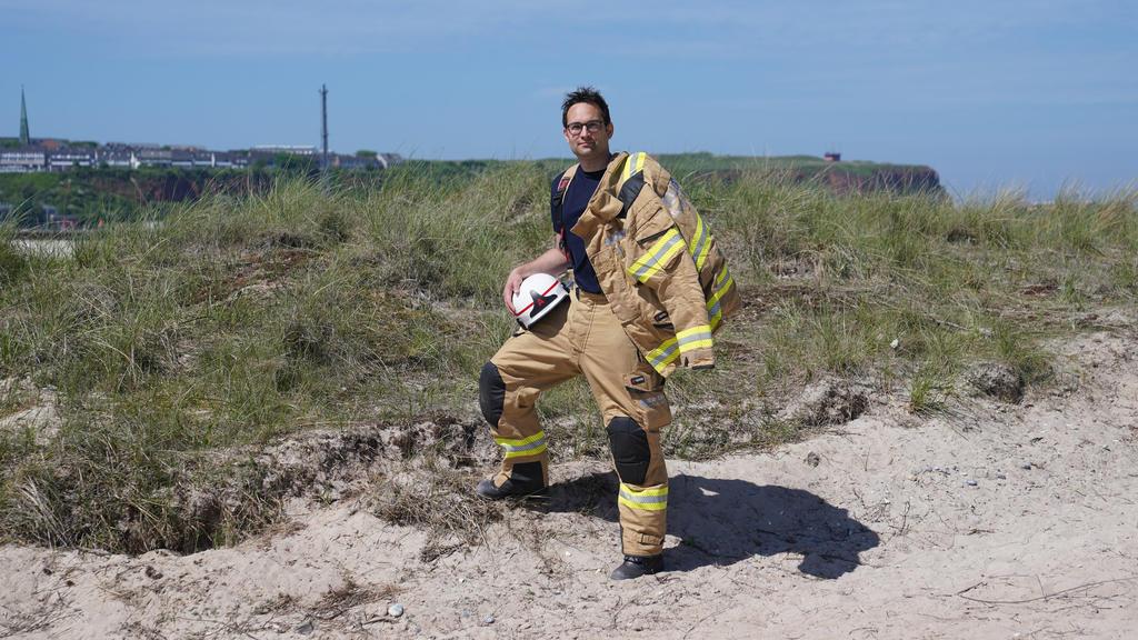 16.06.2021, Schleswig-Holstein, Helgoland: Felix Vorndran von der Freiwilligen Feuerwehr Bergisch-Gladbach steht an der Feuerwehrwache während seines Dünendienstes auf der Düne der Hochseeinsel Helgoland. Angenehmes mit dem Nützlichen verbinden könne