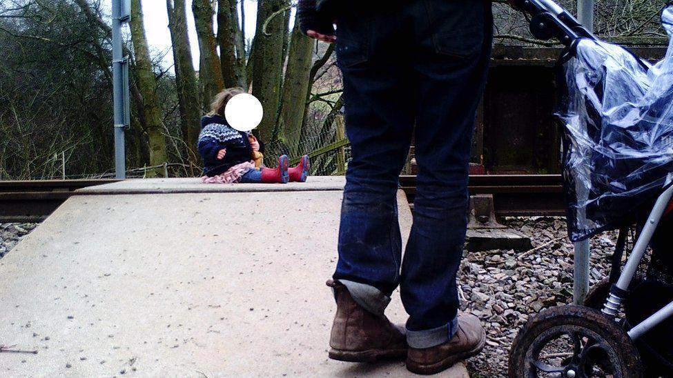 Eltern setzen Kleinkind für ein Foto auf die Gleise