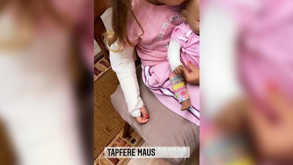 Mia Rose Harrison mit Gipsarm - ihre Puppe trägt als Support auch einen Verband.