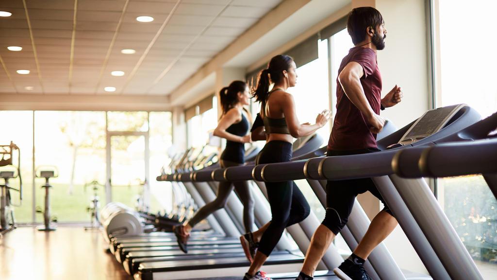 Menschen trainieren im Fitnessstudio auf dem Laufband