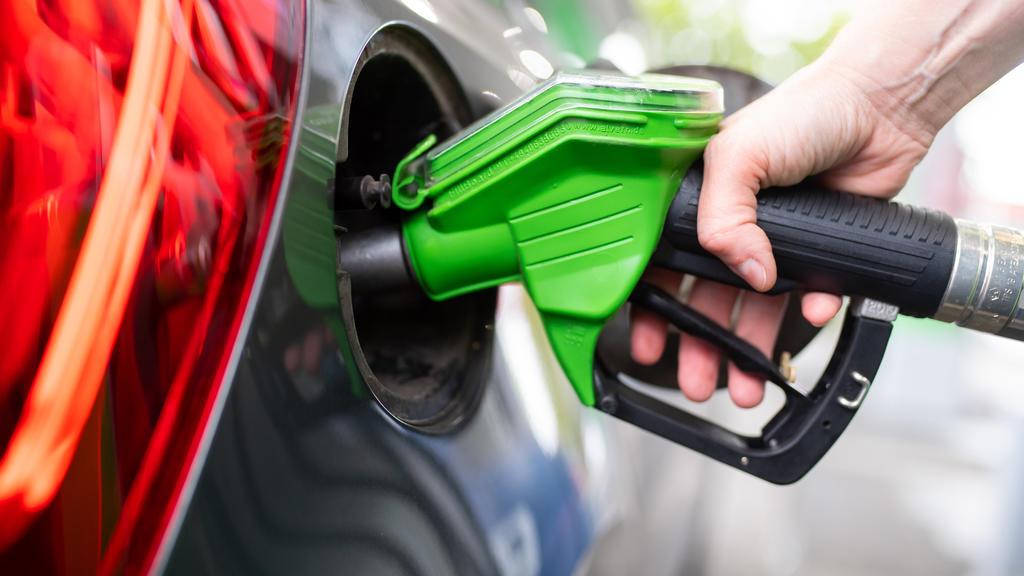 ARCHIV - 06.09.2020, Bayern, München: Eine Frau hält an einer Tankstelle an einer Zapfsäule eine Zapfpistole in der Hand und betankt ein Auto.       (zu dpa «Öl- und Spritpreis auf Mehrjahreshoch») Foto: Sven Hoppe/dpa +++ dpa-Bildfunk +++