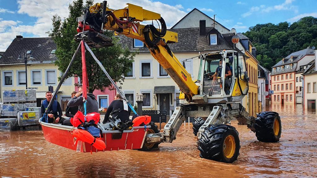 15.07.2021, Nordrhein-Westfalen, Trier: Personen werden mit einem Bagger und einem Boot aus einem überfluteten Teil der Stadt gerettet. Foto: Sebastian Schmitt/dpa +++ dpa-Bildfunk +++