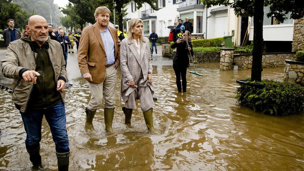 Willem-Alexander und Máxima wirken deutlich betroffen, als sie mit Gummistiefeln durch das knöchelhohe Wasser in Valkenburg waten.