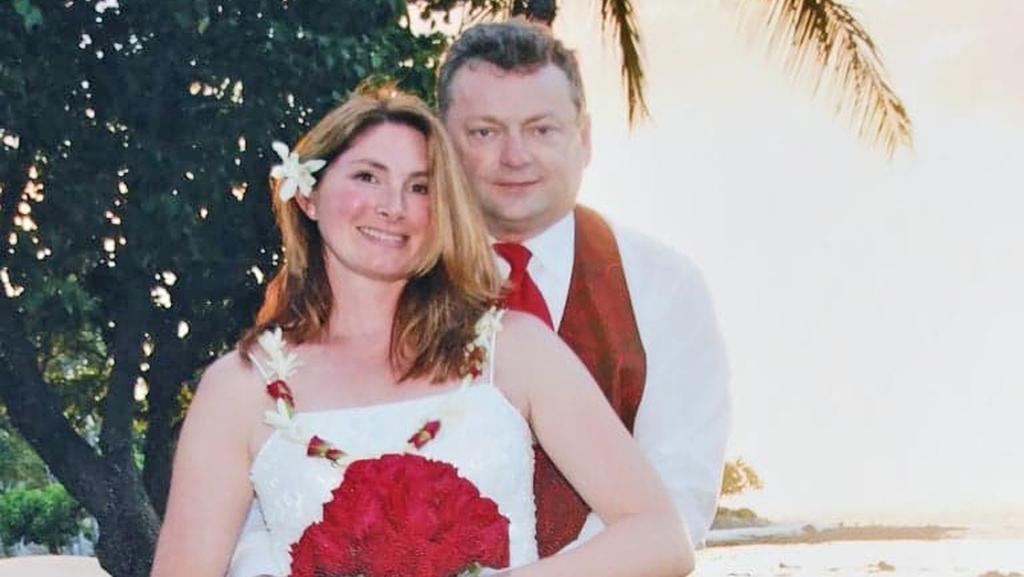 Eine junge blonde Frau wird im Hochzeitskleid von ihrem Bräutigam gehalten.