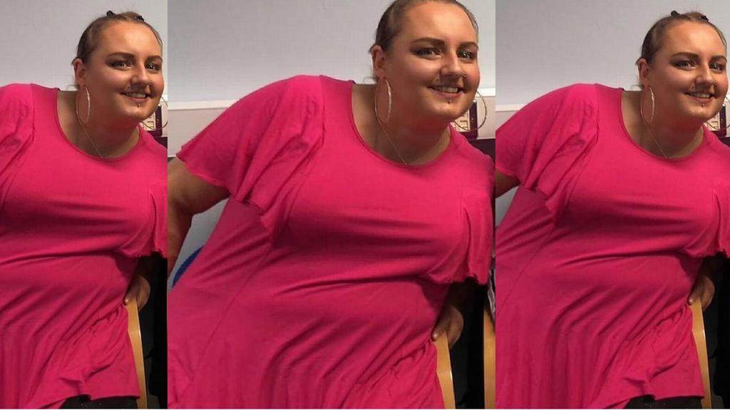 Eine Frau posiert in einem pinken Shirt und ist stark übergewichtig.