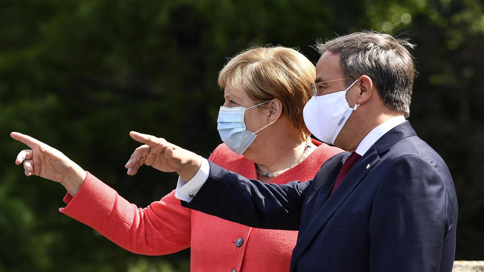 Kanzlerin Angela Merkel (CDU) und Ministerpräsident Armin Laschet (CDU) informieren sich am Dienstagmittag über die Lage im vom Hochwasser stark getroffenen Bad Münstereifel.