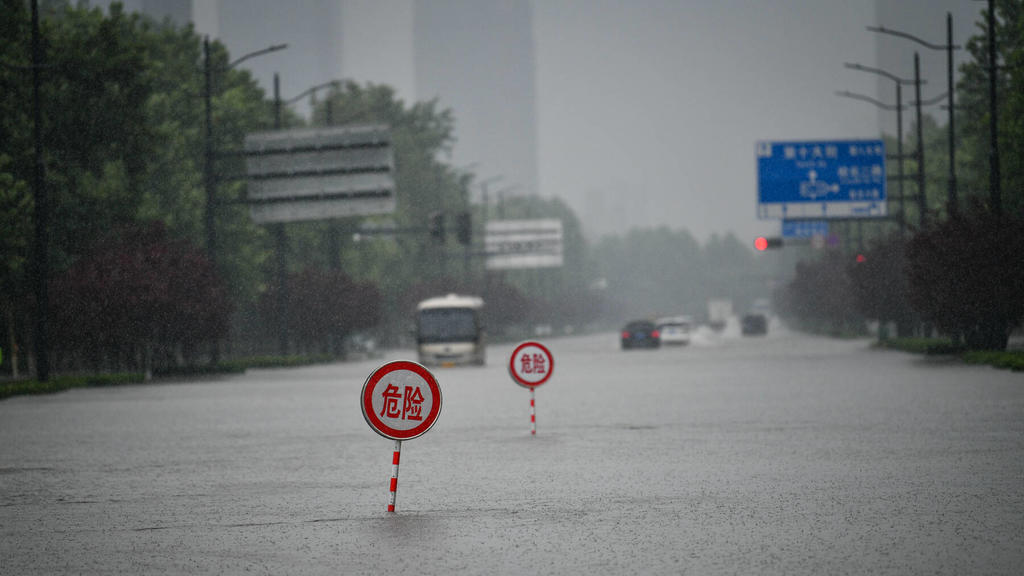 210720 -- ZHENGZHOU, July 20, 2021 -- Danger signs are installed on a waterlogged road in Zhengzhou, capital of central China s Henan Province, July 20, 2021. More than 144,660 residents have been affected by torrential rains in central China s Hena