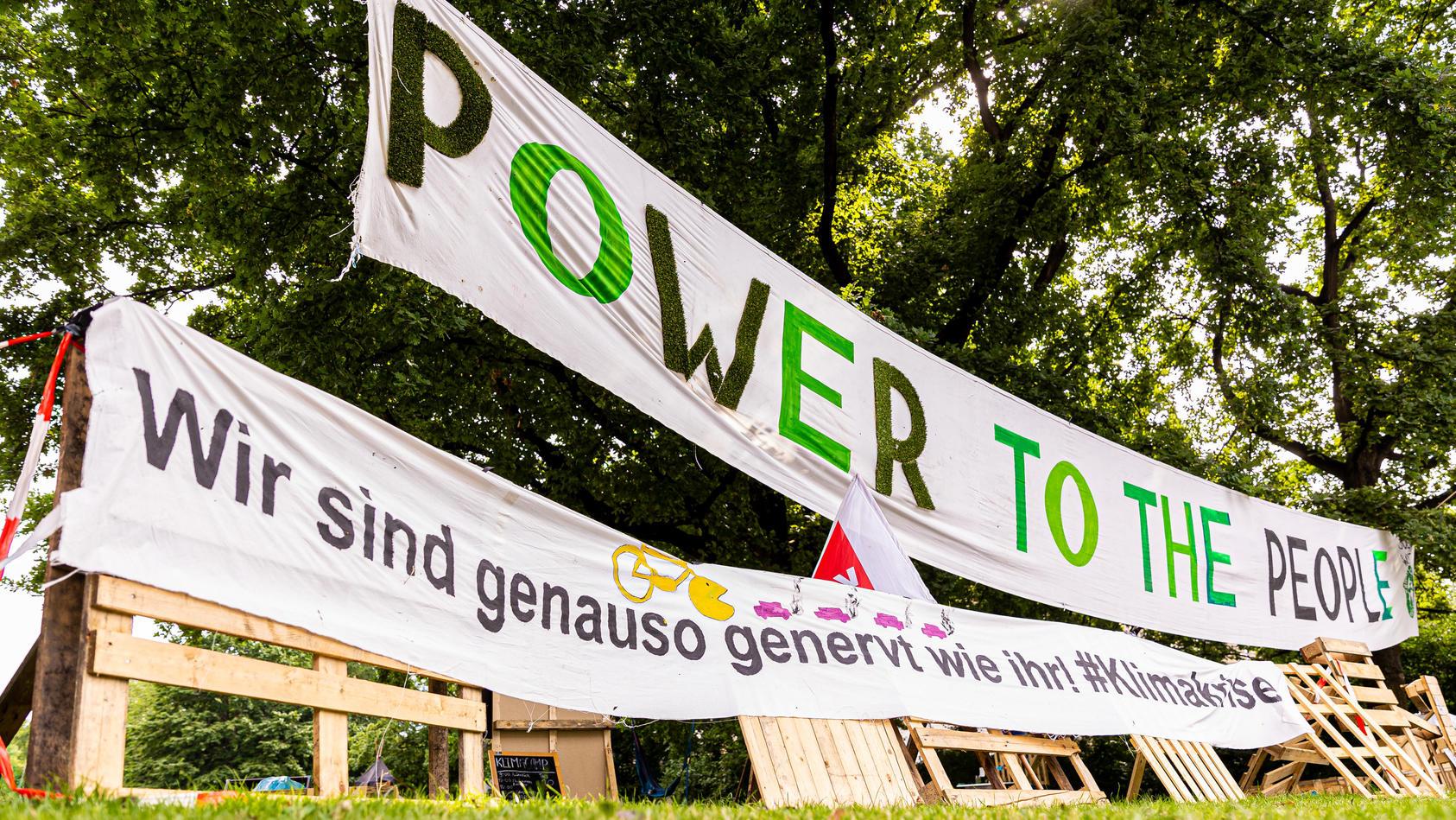 Mit großen Bannern und Plakaten machen die Klimaschützer vor dem Rathaus Hannover auf sich aufmerksam.