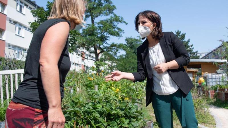 Annalena Baerbock (r) besucht ein Gartenprojekt im Stadtteil Gallus. Foto: Boris Roessler/dpa