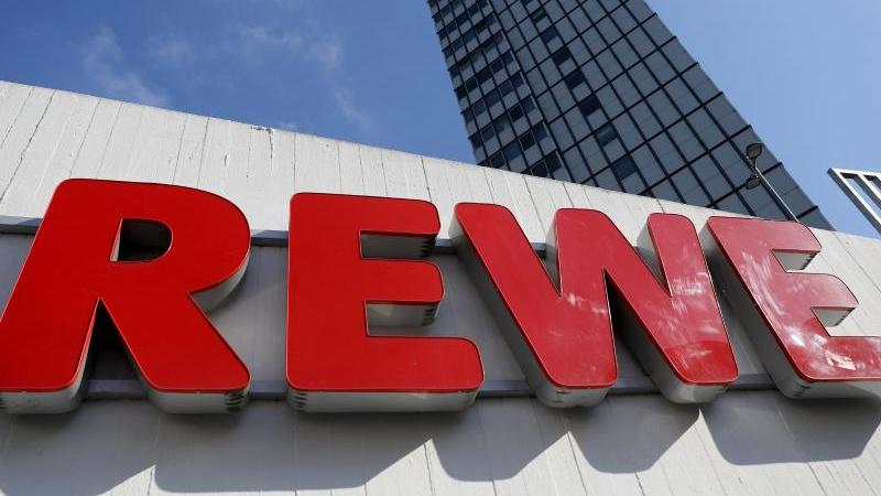 Ein Rewe Schriftzug hängt vor einem Supermarkt.