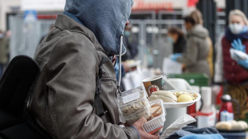 Freiwillige Helfer verteilen Nahrungsmittel an Bedürftige. Foto: Markus Scholz/dpa/Archivbild