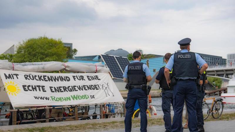 Polizeibeamte stehen an einem Floss der Umweltschutzorganisation Robin Wood. Foto: Paul Zinken/dpa
