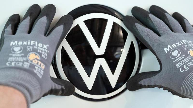 Ein Mitarbeiter setzt das VW Logo in Auto ein. Foto: Sebastian Kahnert/dpa-Zentralbild/ZB/Symbolbild
