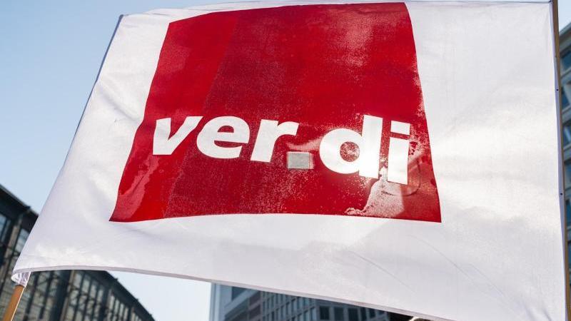EinTeilnehmer eines Streiks schwenkt eine Flagge der Gewerkschaft Verdi. Foto: Christophe Gateau/dpa/Symbolbild