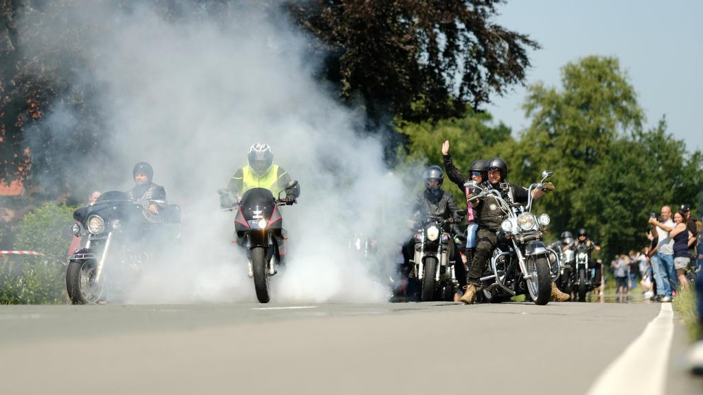 24.07.2021, Niedersachsen, Rhauderfehn: Motorradfahrer fahren am Haus des krebskranken Kilian vorbei. Tausende Biker sind den Aufrufen gefolgt, um dem Jungen noch einmal eine Freude zu bereiten. Mehrere Tausend Motorradfahrer und -fahrerinnen haben s
