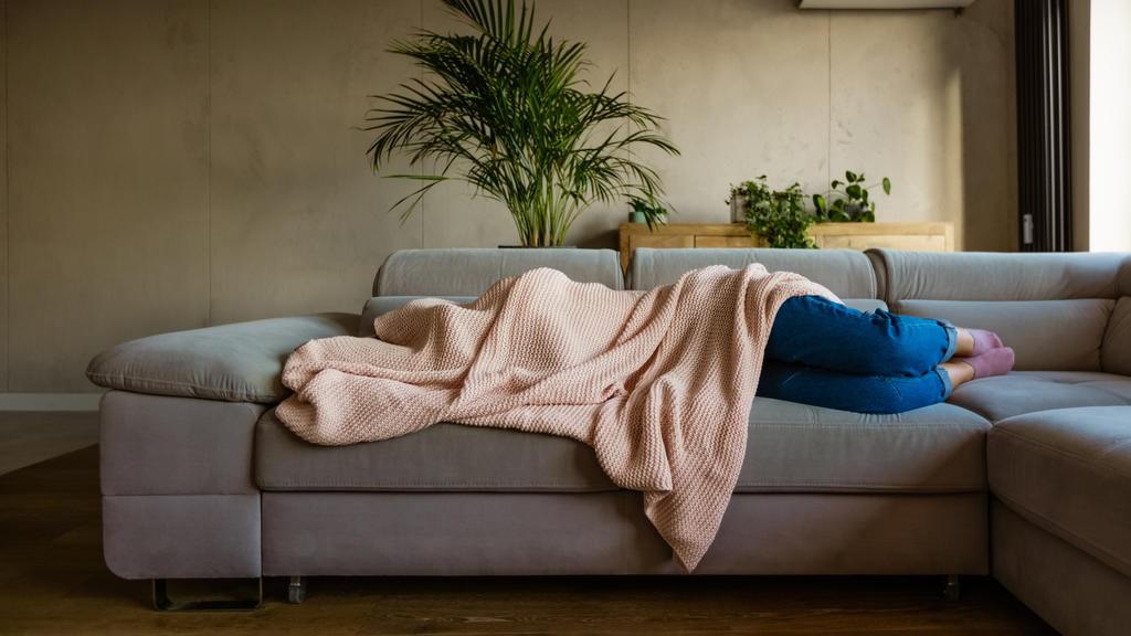 Eine junge Frau liegt auf ihrem Sofa im Wohnzimmer und hat sich die Decke über den Kopf gezogen.