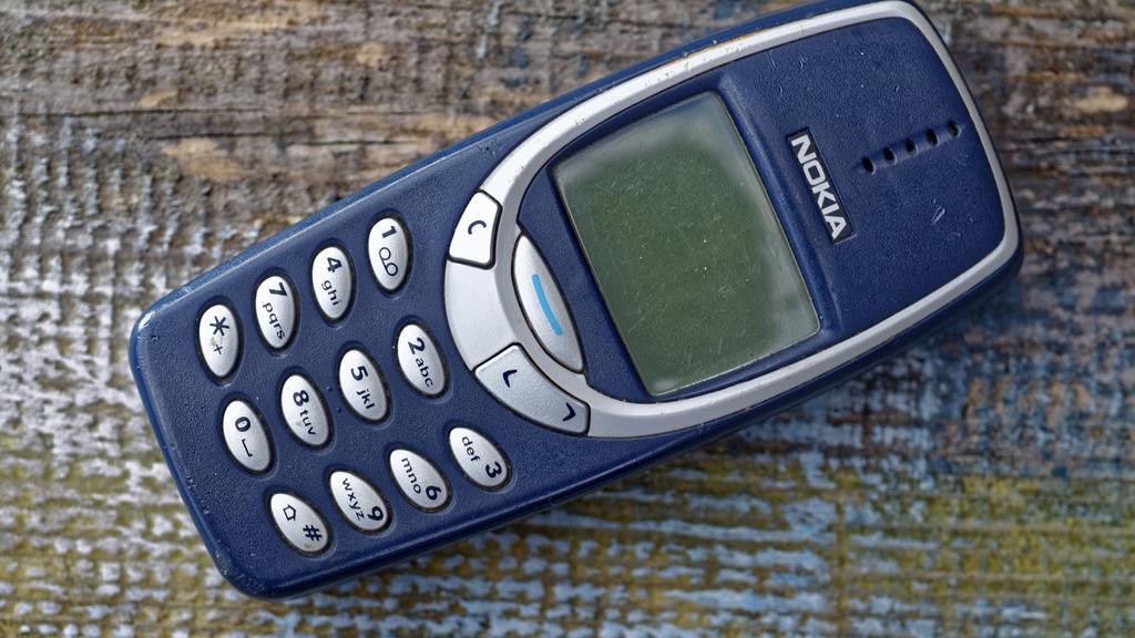 Ein Nokia 3310-Handy liegt auf einem Holz-Untergrund.