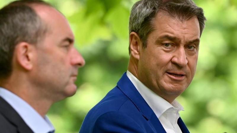 Hubert Aiwanger (l, Freie Wähler) und Markus Söder (r, CSU), stehen vor der Presse. Foto: Peter Kneffel/dpa