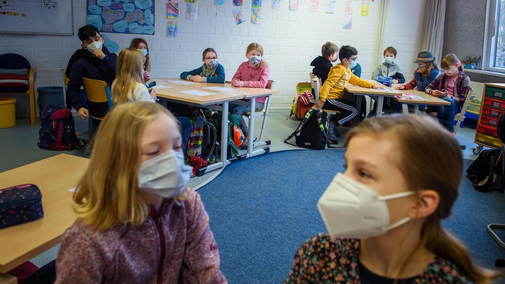 Schüler und Schülerinnen einer 4. Klasse sitzen im Unterricht an der Grundschule Russee in Kiel zusammen an einem Tisch und tragen dabei einen Mund-Nasen-Schutz. Trotz weiterhin verschärfter Kontaktbeschränkungen