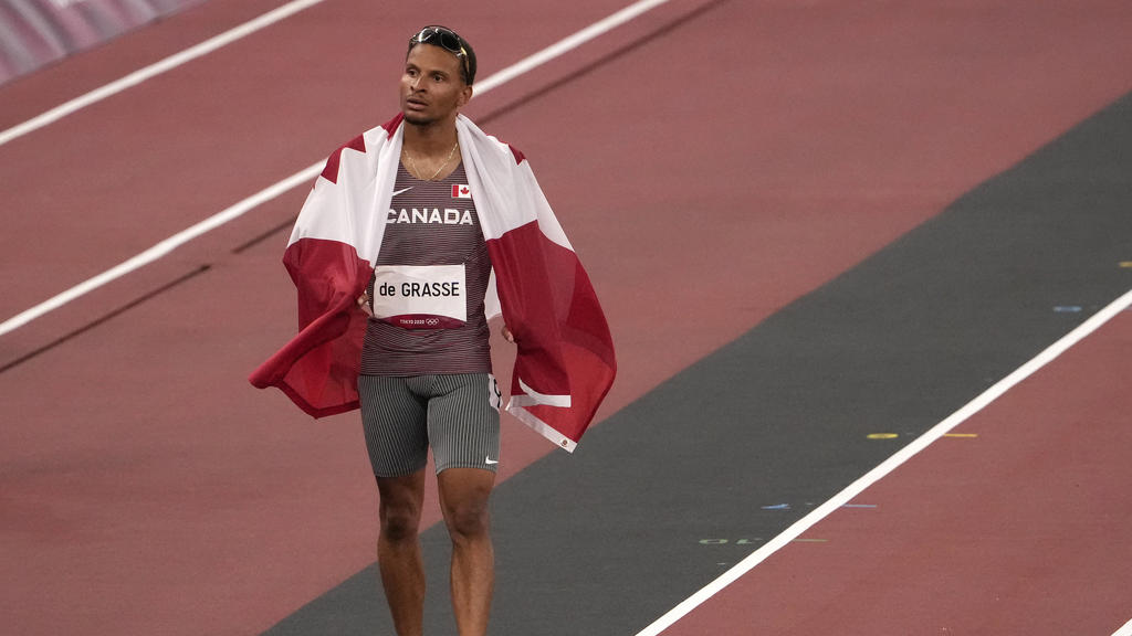 Andre de Grasse, of Canada, bronze, walks on the track after the final of the men's 100-meters at the 2020 Summer Olympics, Sunday, Aug. 1, 2021, in Tokyo, Japan. (AP Photo/Martin Meissner)
