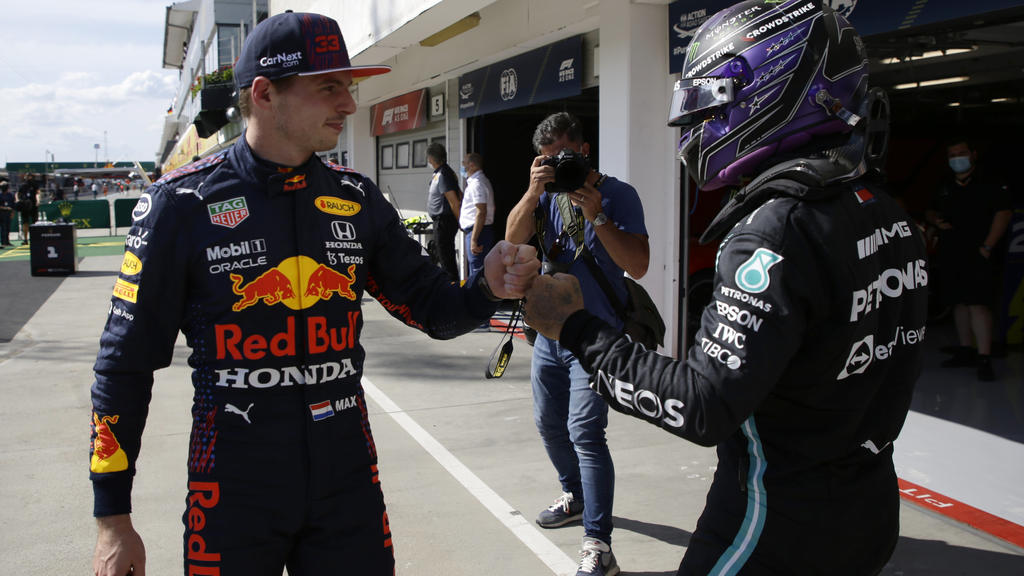 Mercedes driver Lewis Hamilton of Britain, right, after setting a pole position fist bumps with third placed Red Bull driver Max Verstappen of the Netherlands after the qualifying session for the Hungarian Formula One Grand Prix, at the Hungaroring r