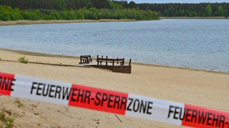 Mit einem Flatterband ist ein Zugang zum Strand des Helenesees abgesperrt. Foto: Patrick Pleul/dpa-Zentralbild/dpa/Archivbild