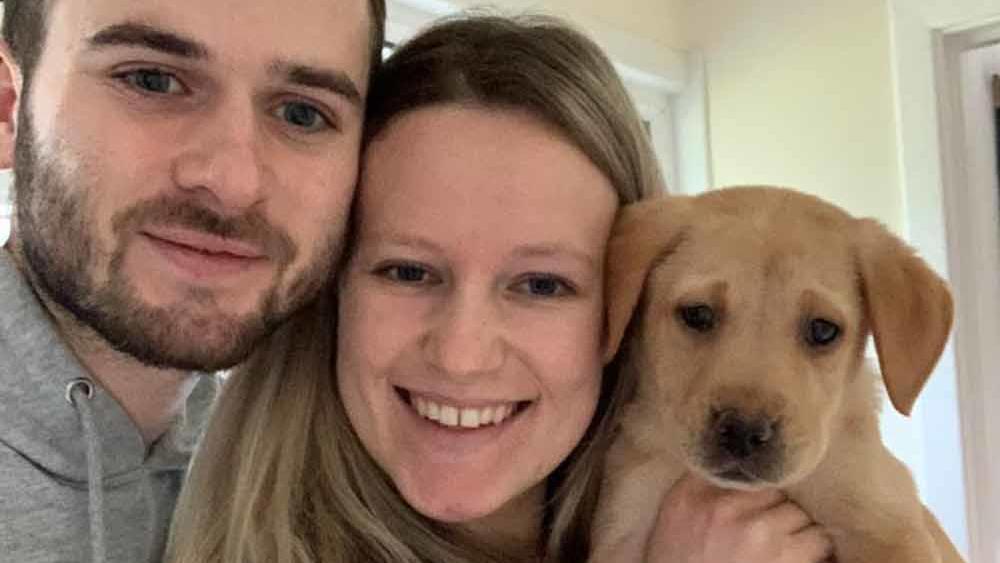 Kate und Ryan halten ihren Labrador-Welpen Coby in die Kamera und lachen.