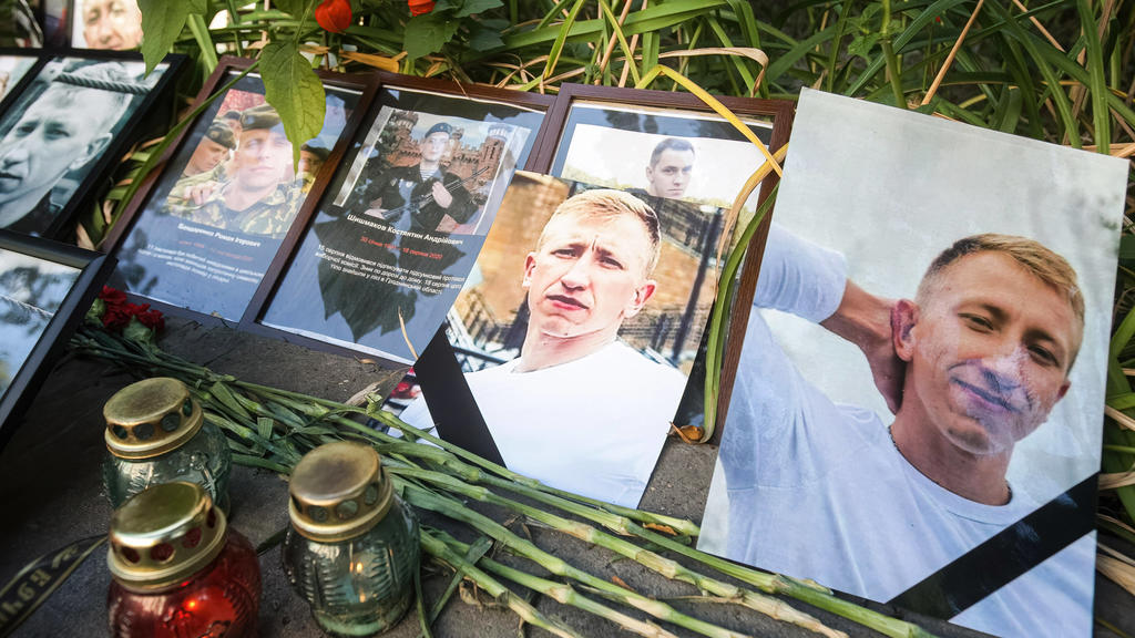 August 3, 2021, Kiev, Ukraine: Flowers and candles are left with photos of Belarusian opposition activist and Head of the Belarusian House in Ukraine Vitaly Shishov outside the Belarus Embassy during a protest in his memory..Belarusian activist Vita