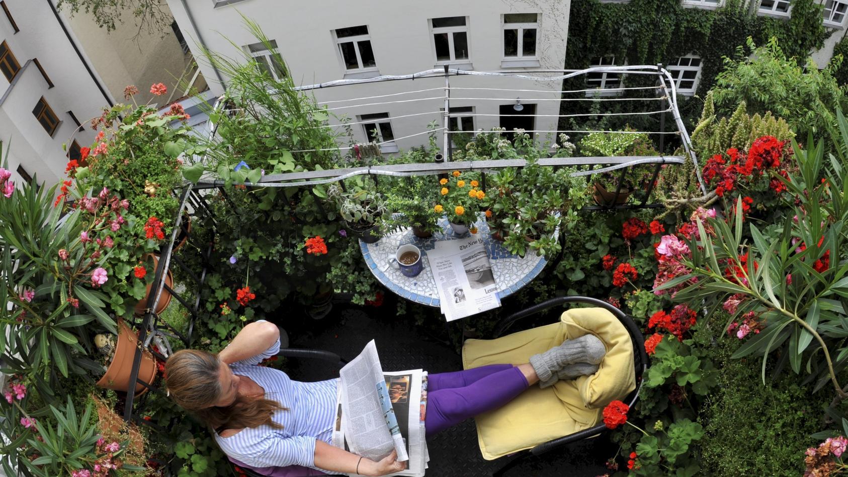 Eine Frau liest auf dem Balkon ein Buch.